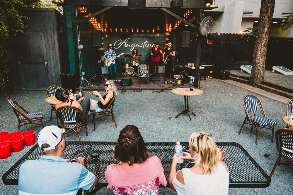 People watch band on outdoor stage at Augustine bar in Austin Texas