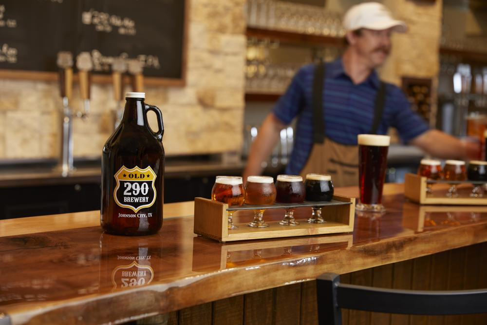 Photo of a beer growler reading Old 290 Brewery Johnson City, TX next to a tasting flight of beer on wooden bar and a bartender in white baseball cap behind the bar at Carter Creek Winery Resort