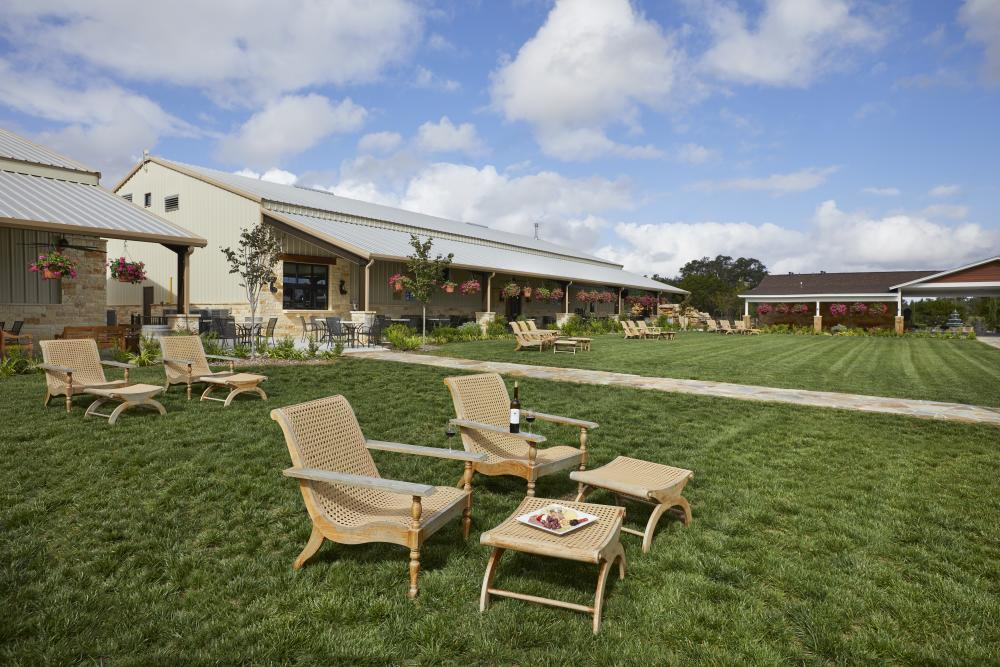 Photo of the Pavilion Lawn at Carter Creek Winery Resort & Spa with wooden chairs in the front and footrests and a plate of charcuteries and bottle of wine