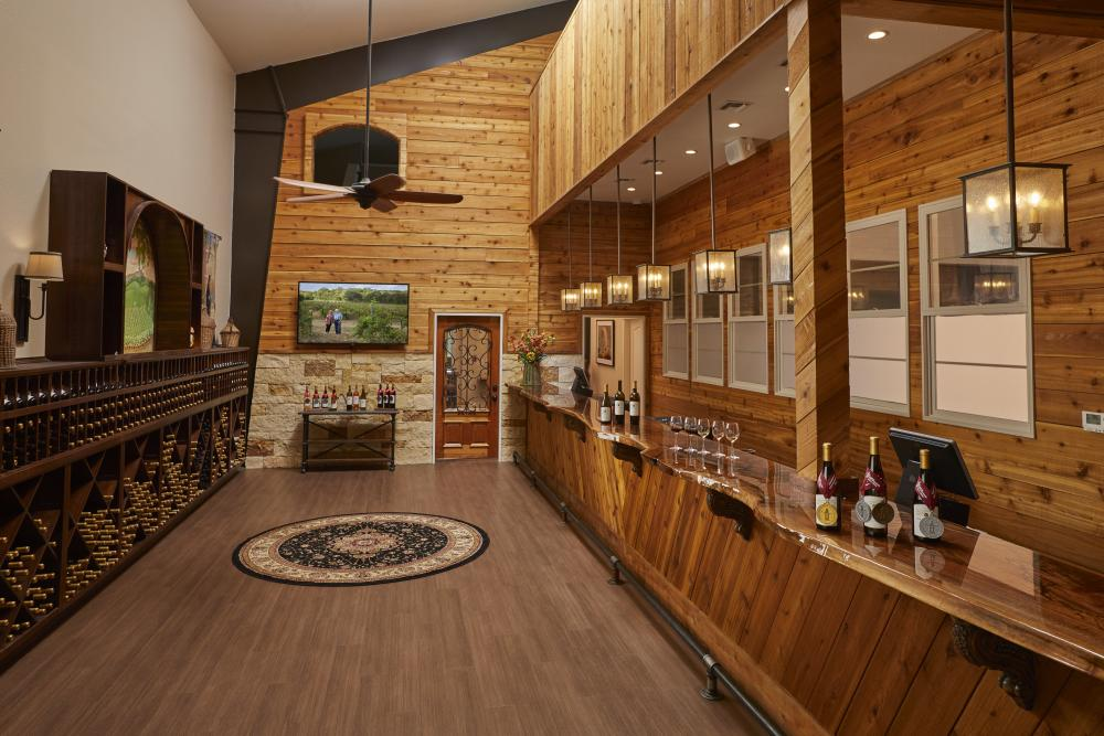 Photo of wooden winery bar at Carter Creek Winery Resort & Spa with bottles on wine on the bar, and racks of wines across from the bar