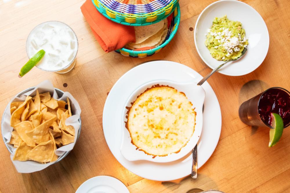 Table of food at El Naranjo including queso, guacamole, a bowl of chips, tortillas and a margarita