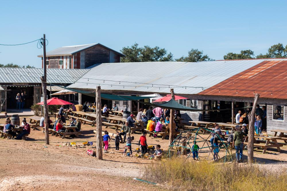 Children playing in a large sand pit at Jester King Brewery in front of the Pole Barn