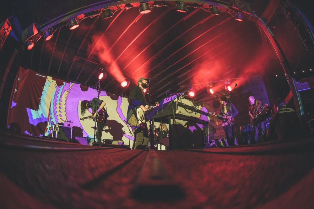 Photo of a band on stage using a fisheye lens. Photo shows four men playing guitars and one man playing the drums, there is a digital projection on the wall behind them and red lights on the stage