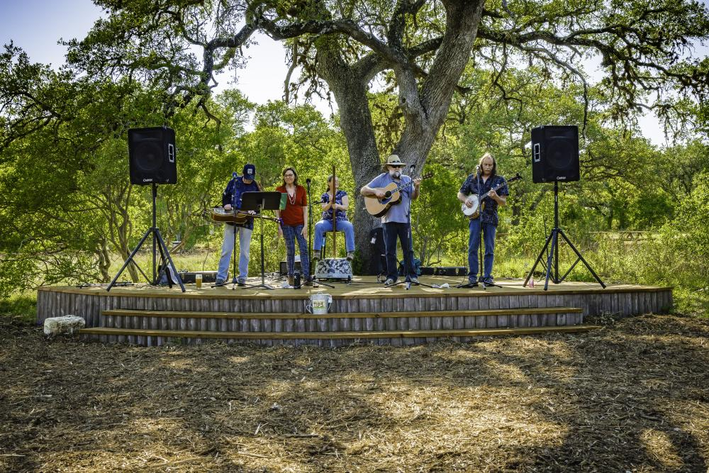 Five members of a bluegrass band play on the outdoor stage under a large tree at Vista Brewing