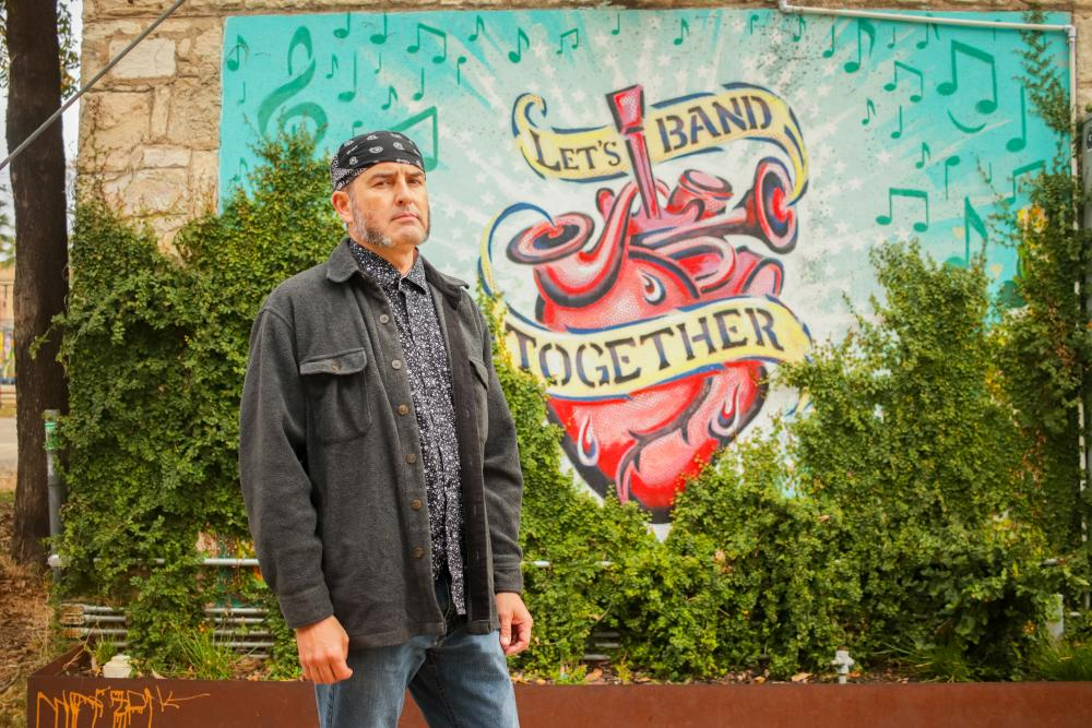 artist Federico Archuleta in front of his mural called Lets Band Together