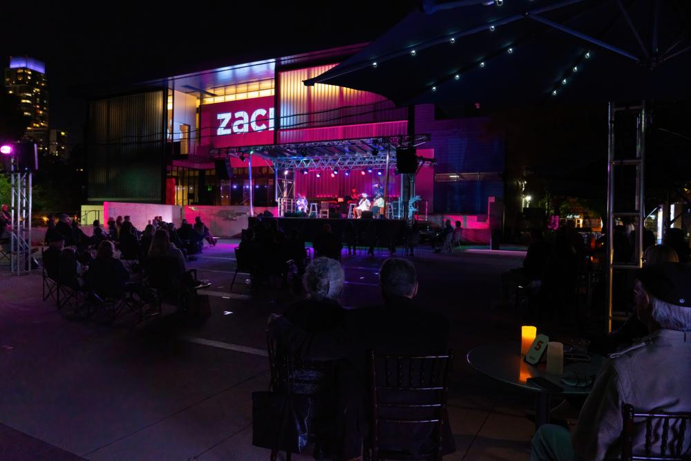 Photo of a performance of Gospel Down By The Riverside ZACH Theatre. The show is being held outside at night, and people are seated at tables in front o the building