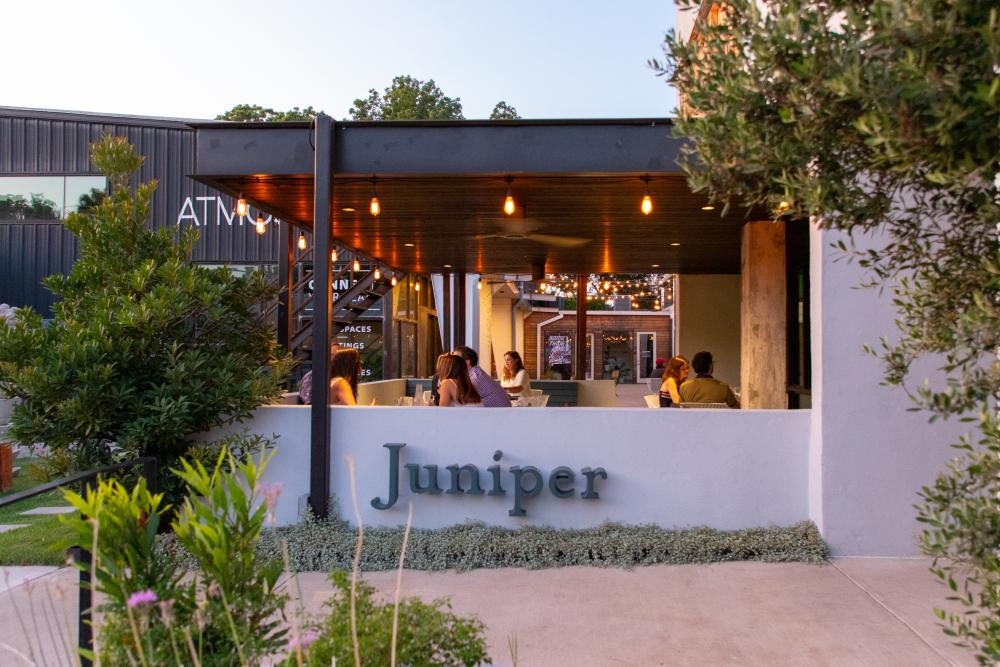 People dining on the patio at Juniper restaurant in Austin Texas