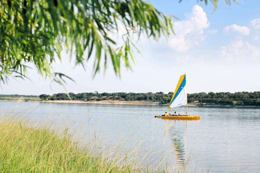 Photo of a sailboat on Boerne City Lake, viewed from the shoreline in Boerne Texas