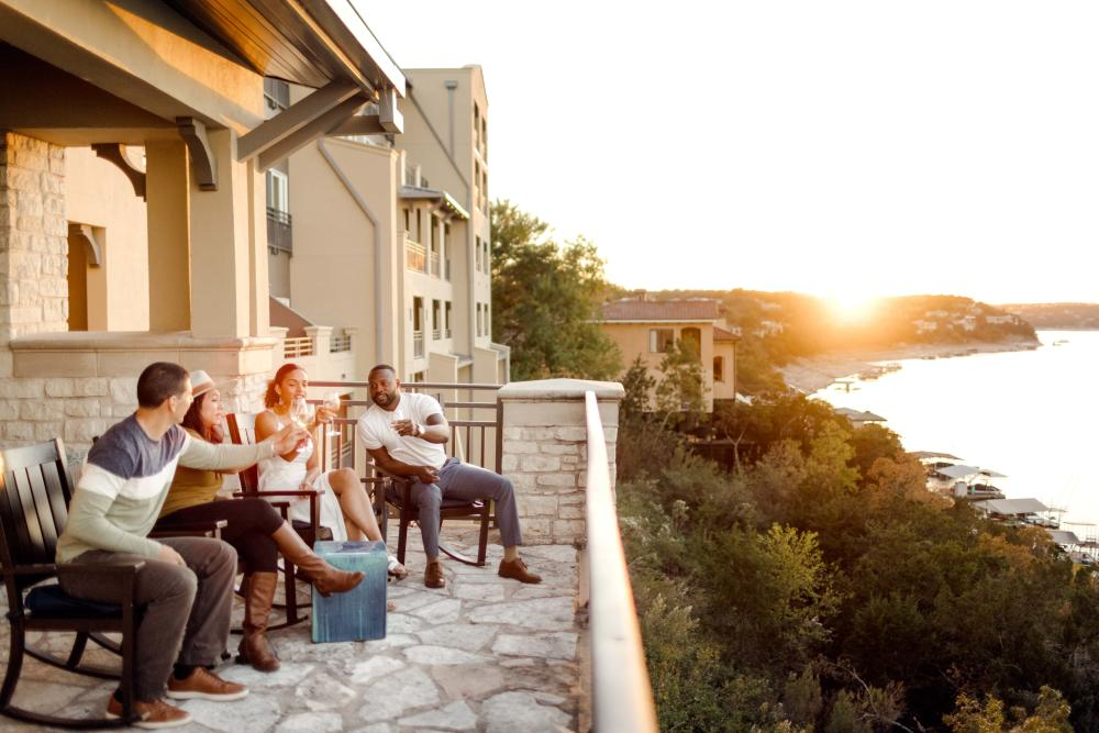 Four people enjoy drinks with a Sunset view from patio at Lakeway Resort and Spa