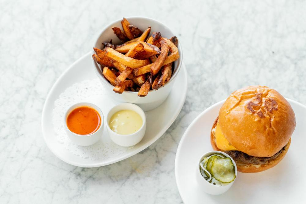 Plancha burger with fries and three side sauces at Launderette in Austin Texas