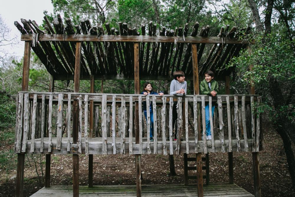 Children playing on wood structure on nature trail at Omni Barton Creek Resort and Spa in Austin Texas