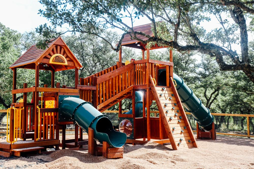 Photo of a large wooden playground at Family Business Beer Co with three plastic slides and a small rock climbing area