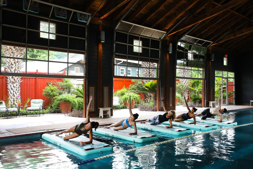 Five people doing side plank pose at Pool Barn Yoga Class at Lake Austin Spa Resort in Austin Texas