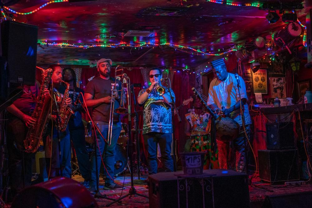 Photo of 5 men in a band on stage at the Sahara Lounge. The room is dark and rainbow rope lights surround the ceiling. From left to right person playing baritone sax, man playing alto sax, man holding trombone, man playing trumpet, man playing kora