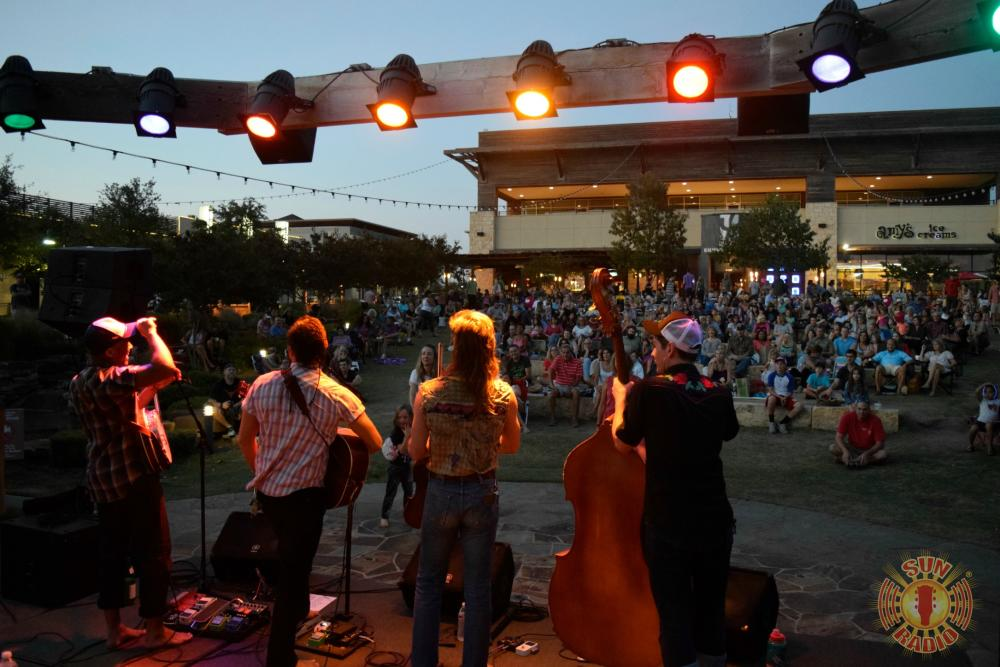 Band on stage looking towards crowd at the Saturday Night Concert Series at the Hill Country Galleria