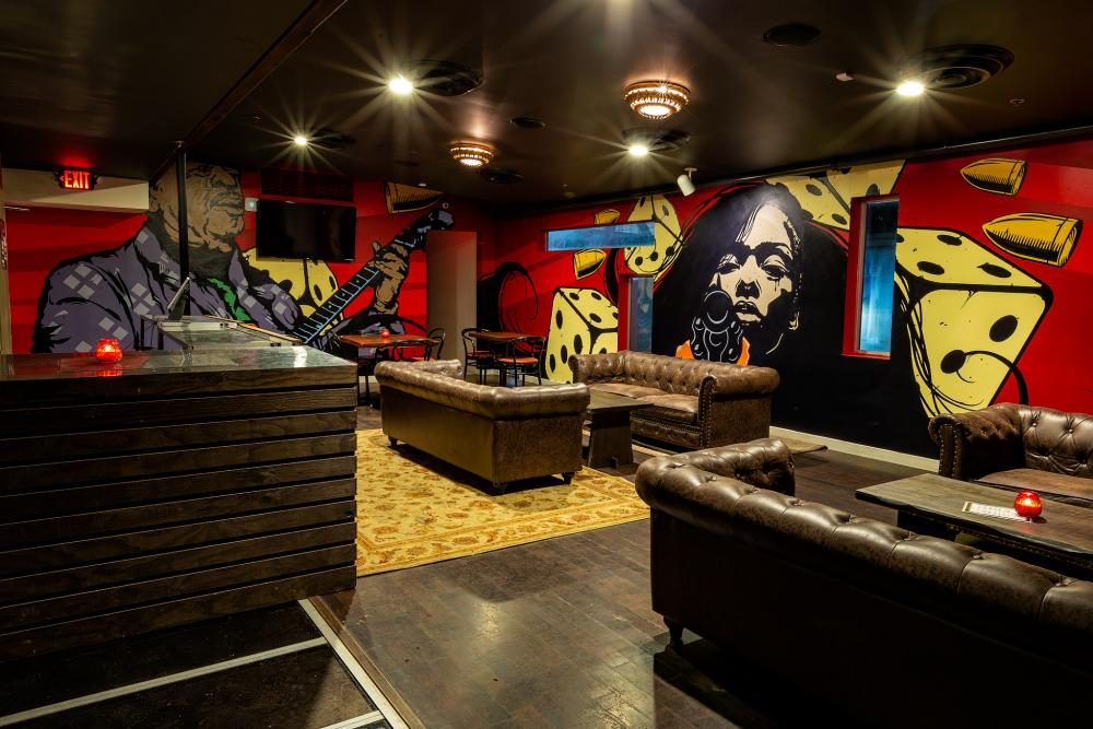 Stagger Lee bar interior with murals on walls and leather couches