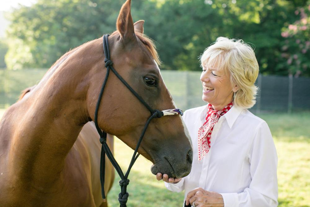 Photo of a blonde woman in a white shirt looking at a brown horse with a loose, black horse lead rope around its face