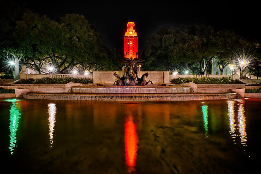The University of Texas fountain and Tower lit up orange in Austin Texas