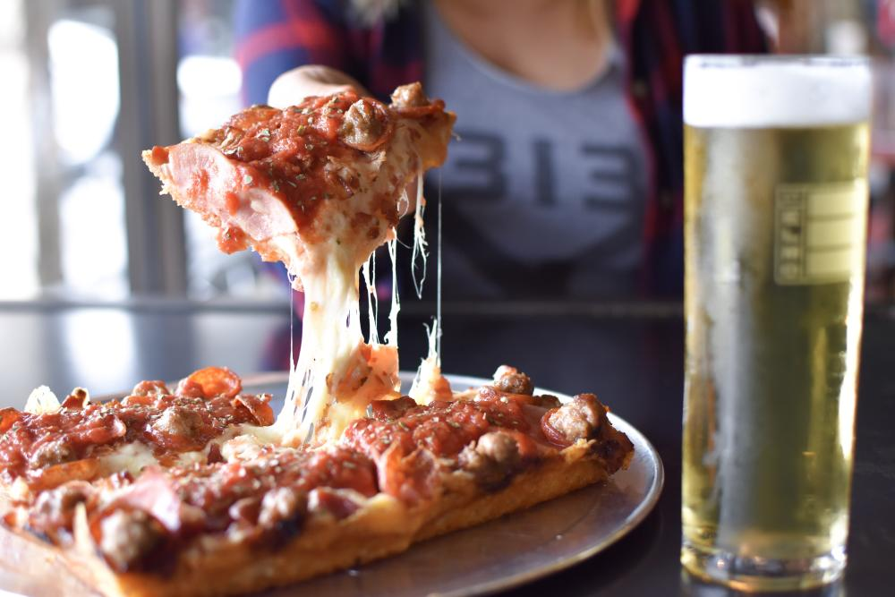 Photo of a person holding a slice of pepperoni and sausage pizza towards the camera. A pale lager beer is on the table