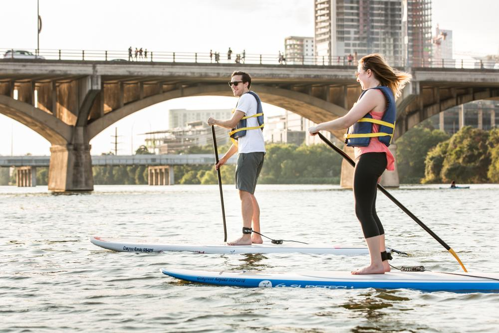 Man And Woman Stand Up Paddle Boarding on Lady Bird Lake In Austin, TX