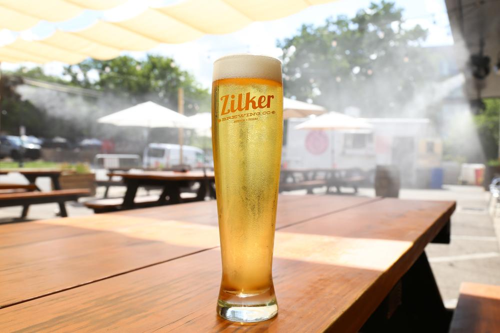 Photo of a tall glass of pale beer on a patio table at Zilker Brewing Company. There is a sun shade above and misting fans in the backround