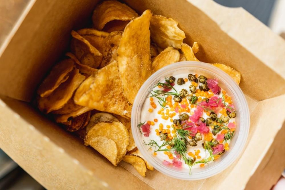 Smoked Salmon Sour Cream Dip and chips in takeout container from Drop Kick in Austin TExas