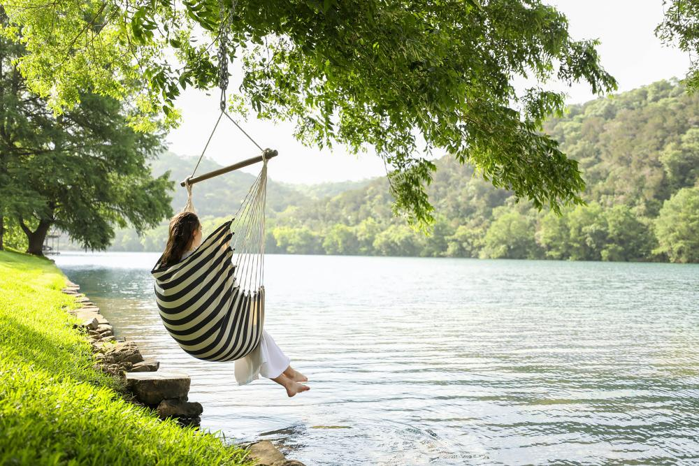 Woman sitting in hammock over the Lake at Lake Austin Spa Resort in Austin Texas