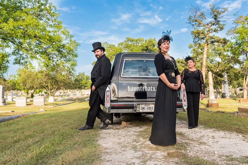 Photo of two women and a man standing in a cemetery and leaning up against a black hearse which says Haunted ATX