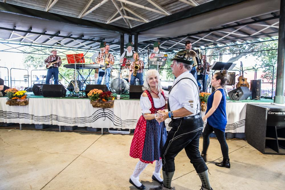 A man and woman wearing traditional Bavarian German outfits dance in front of a stage with musicians at Fredericksburg Oktoberfest