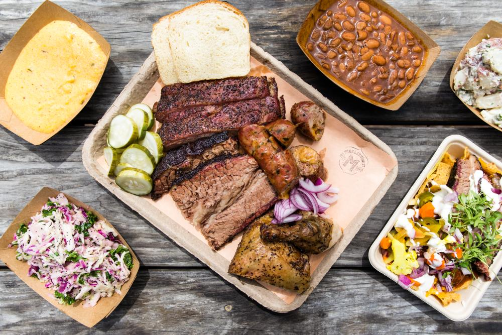 Overhead view of a platter of bbq meats and sides like beans, slaw, grits and potato salad
