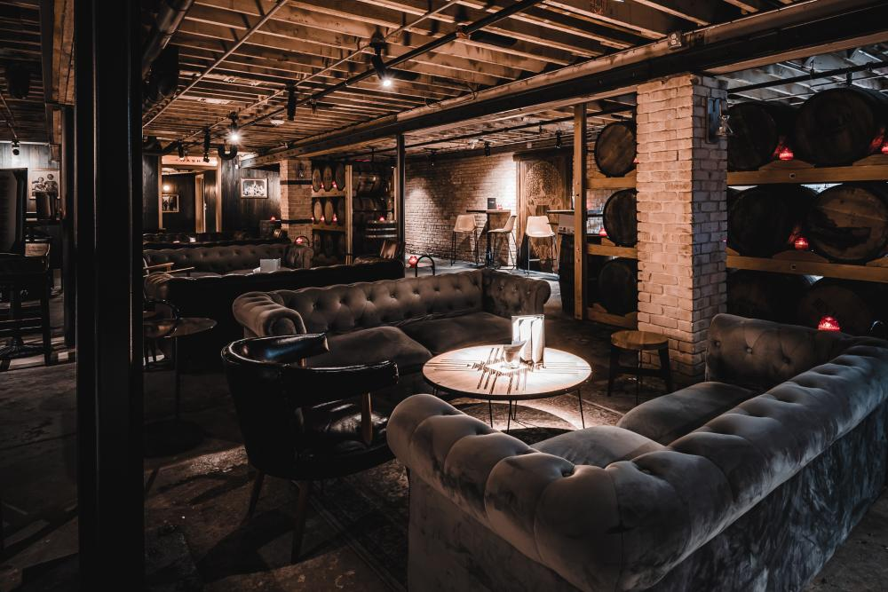 Interior of DuMonts Down Low basement bar with dark couches and whiskey barrels in Austin Texas