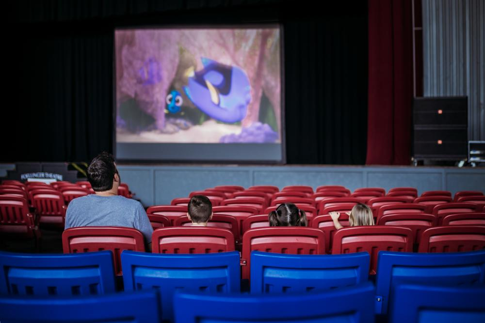 A father, two daughters, and one son sit in red chairs to watch Finding Dory at the Foellinger Theatre