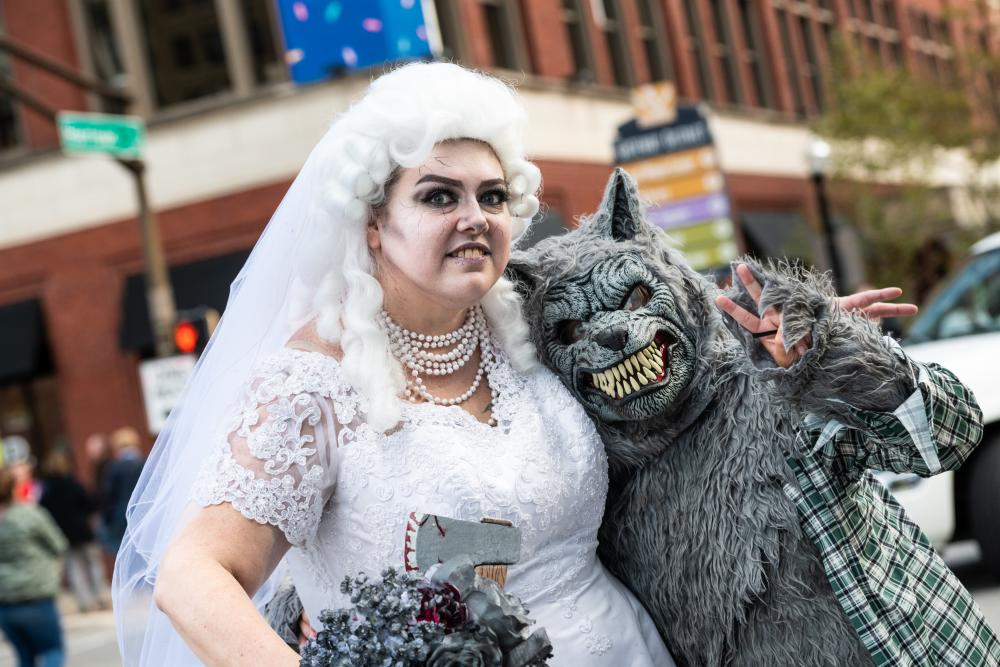 couple in halloween costumes as a zombie bride and warewolf
