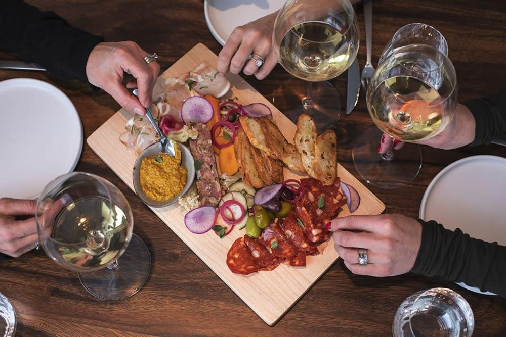 Three sets of hands reach for food from a charcuterie board filled with meats, vegetables, and fruit at the Modest Butcher