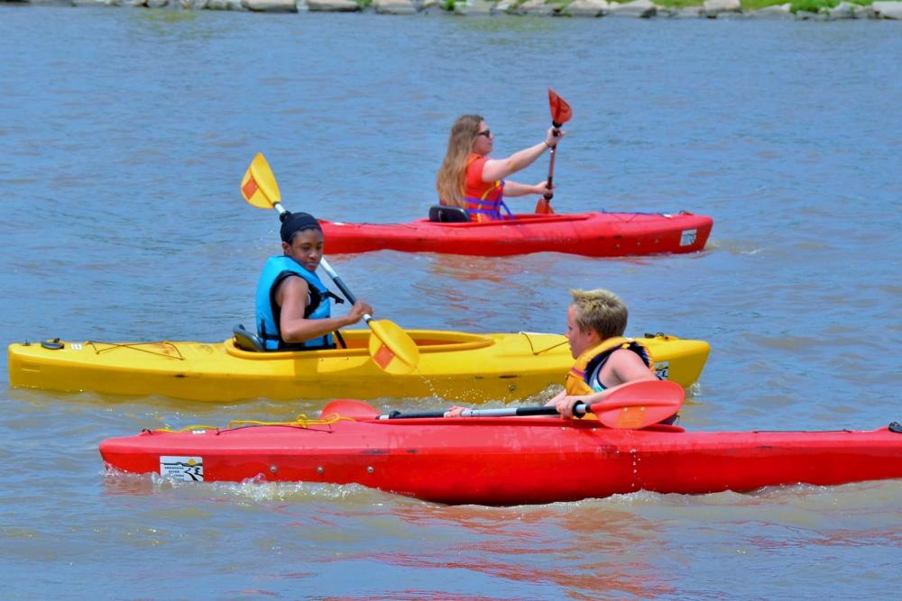 People kayaking in red and yellow kayaks on the Arkansas River in downtown Wichita