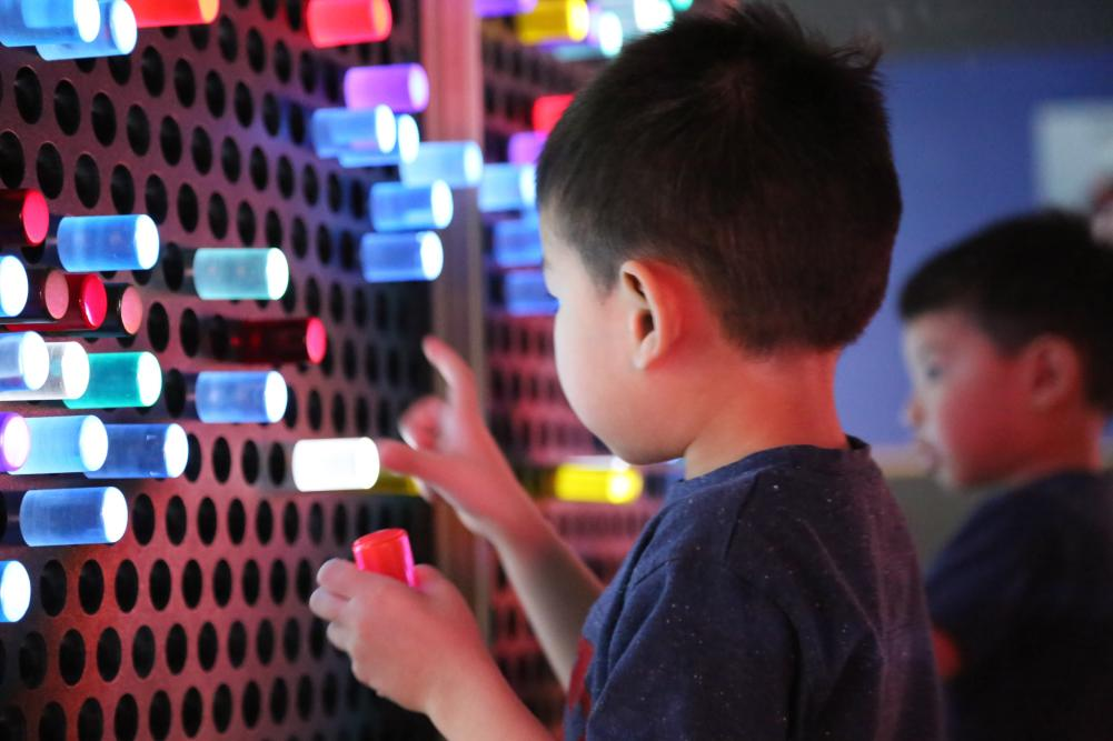 Child playing with light exhibit at the Thinkery Museum in Austin Texas