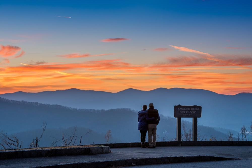 A couple enjoys a mountain vista on the Blue Ridge Parkway near Asheville, NC
