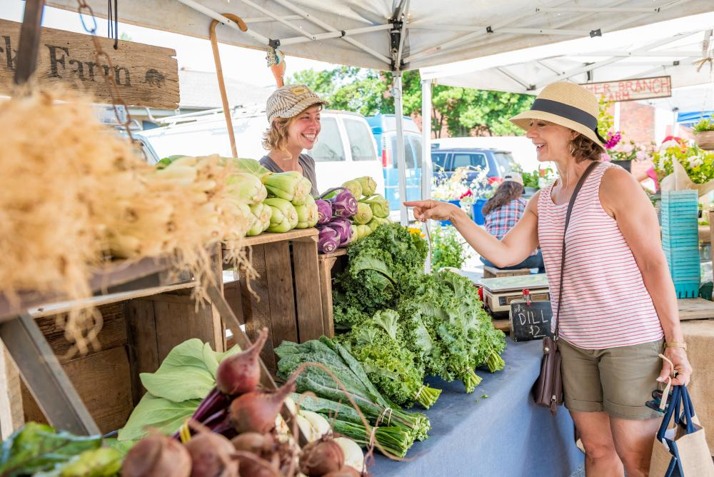 A woman shops for farm fresh vegetables at an open air tailgate market in Asheville, NC