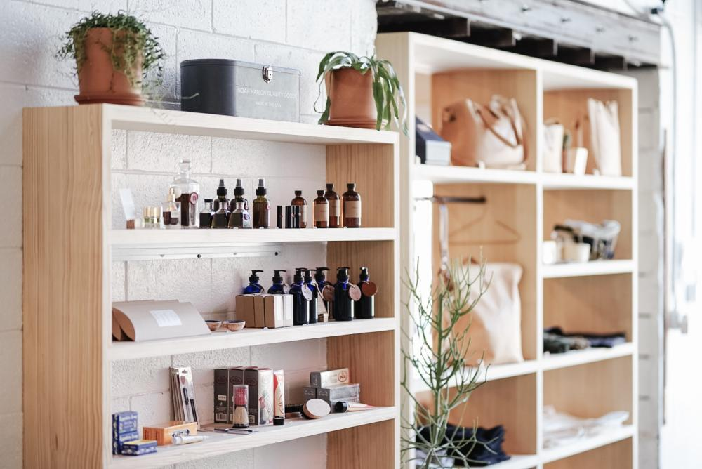 two blonde wood shelves with various products like soaps, sprays, oils and leather bags at the Noah Marion store in Austin Texas