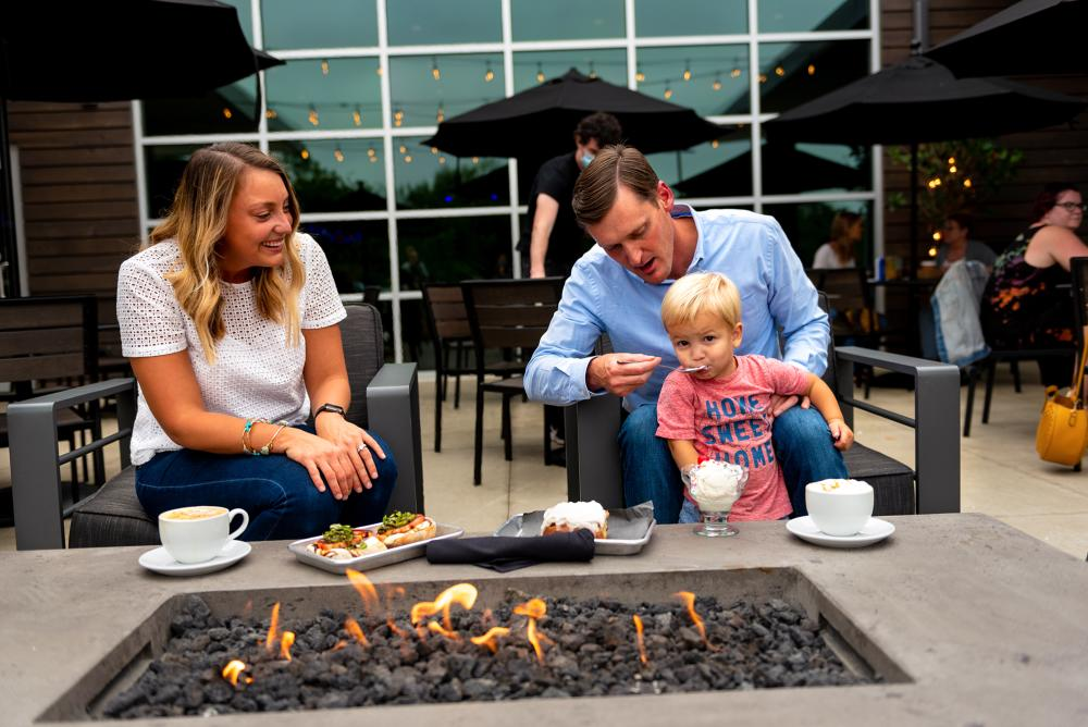 family eating on the outdoor patio by the firepit at the Club Room at the Clyde in Fort Wayne