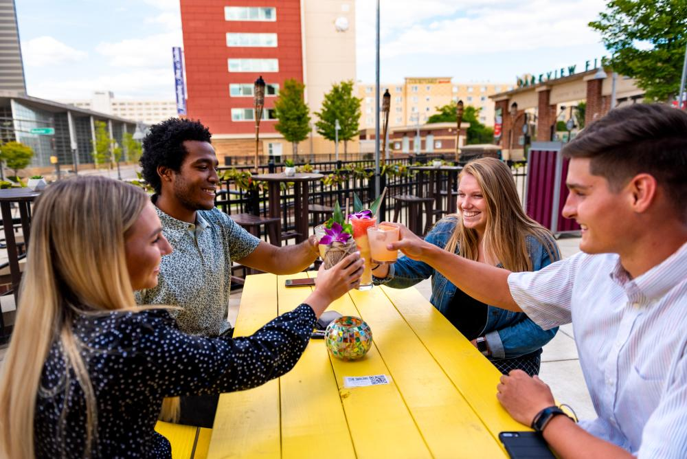 Young adults enjoying drinks at the Sidecar outdoor bar in downtown Fort Wayne.