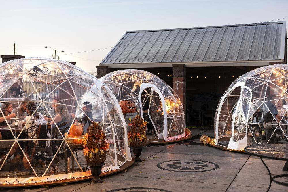 Igloos provide heated outdoor fall dining on the patio at Three Rivers Distillery