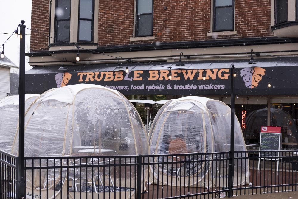 Family dining in a heated outdoor winter bubble at Trubble Brewing in Fort Wayne