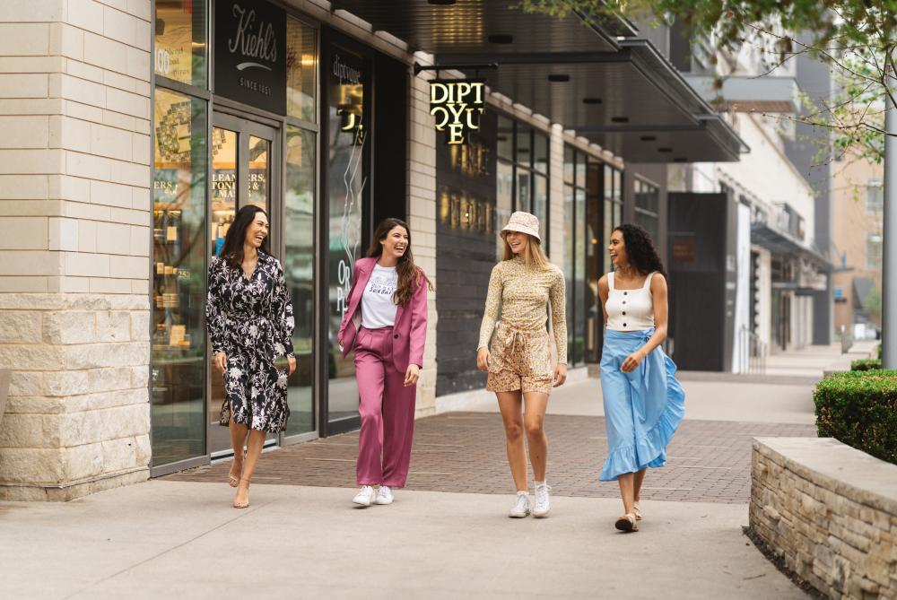 Four women walking together on sidewalk at Domain Northside outdoor mall near Kiehl's storefront