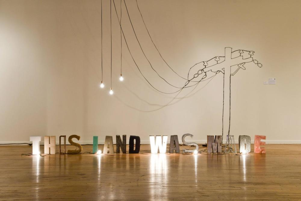 Multimedia artwork reading This Land was Made by Jorge Galvan at Mexic-Arte Museum in Austin Texas