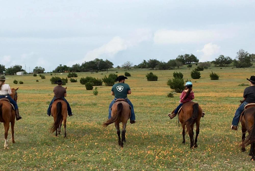 Horseback riders cross a field with Bit and Bridle Stables in Fredericksburg, TX