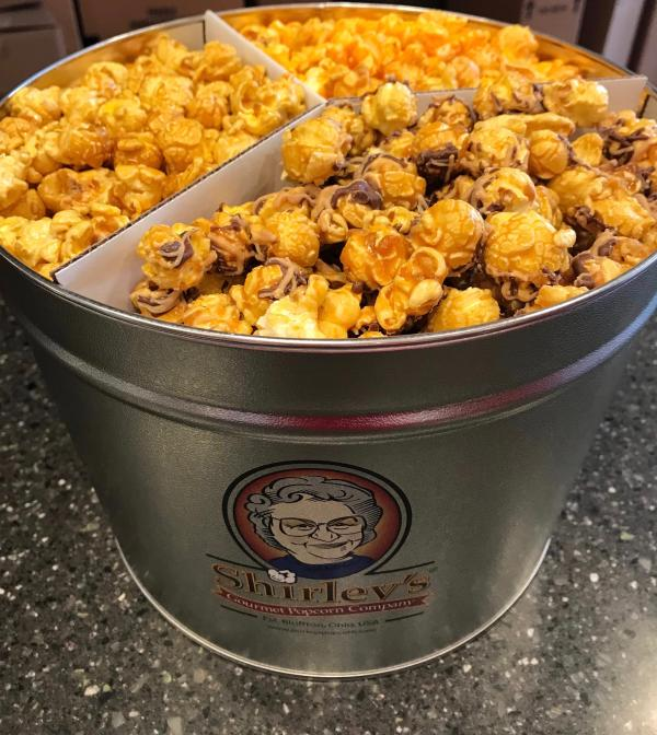 Three different flavors of popcorn in a tine from Shirley's Popcorn