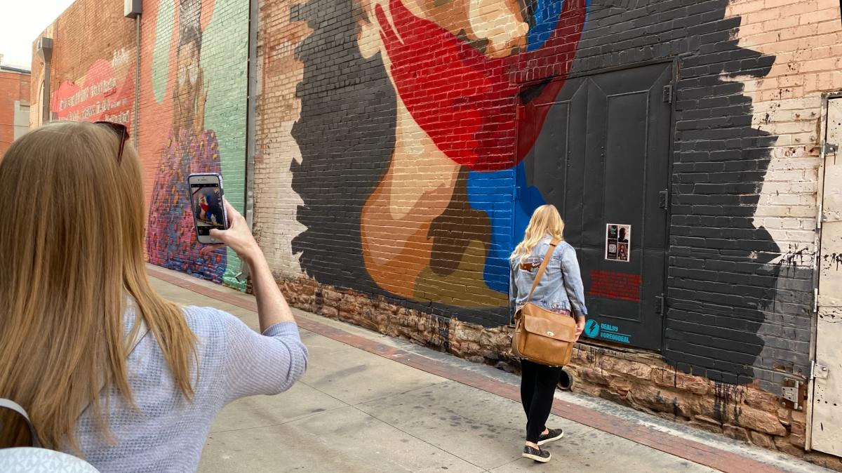 Woman taking a photo of a woman in front of Street Wise Murals Behind Boulder Theater