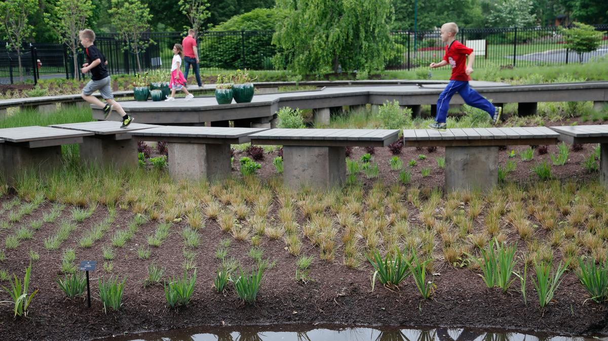 Kids cross the walkway at wetland explore at The Scotts Miracle-Gro Foundation Children's Garden at Franklin Park Conservatory