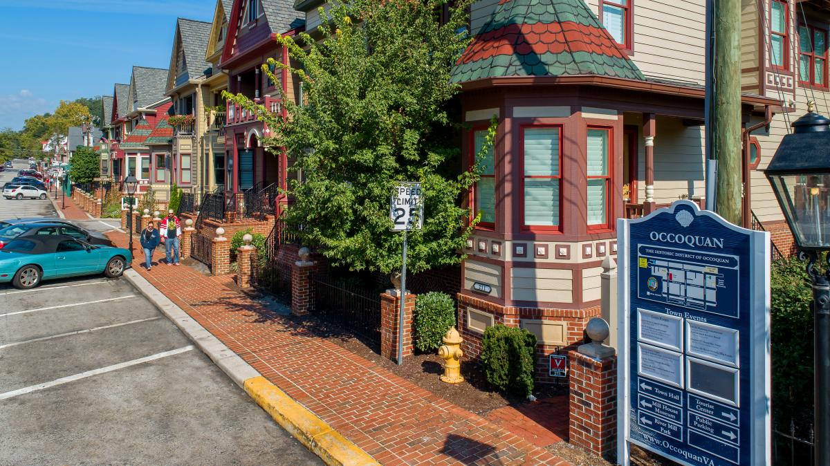 couple walking on a brick sidewalk in front of historic homes in Occoquan
